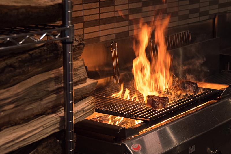 キッチンで豪快に薪焼きされるステーキ