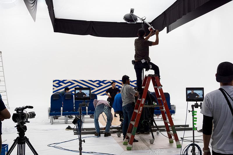 機内安全ビデオの撮影現場。機内さながらにシートが並ぶスタジオ