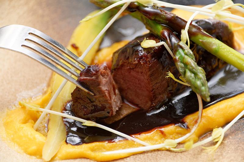 野生イノシシのステーキ。ポテトとニンジンのチェダーソースに、アスパラなどが添えられている
