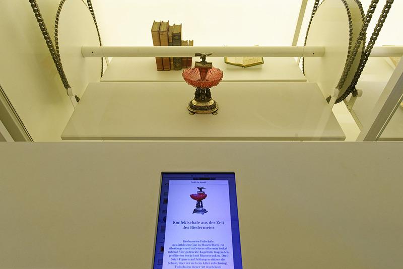 調度品が昇降台でゆっくり動いている。手前にあるタブレットで品々の詳細が分かる