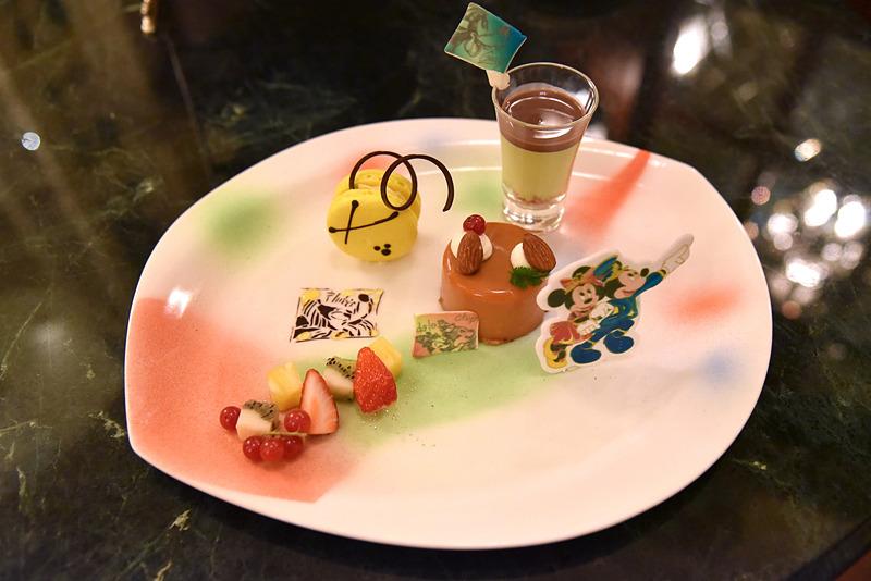 ミッキーマウスたちが未来へと進む姿のパスティヤージュがワンポイントのデザート皿には「キャラメルナッツムース」「ピスタチオムースとチョコレートスープ」「オレンジマカロン」