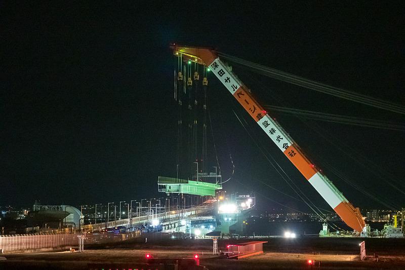 吊り上げられた状態で橋の上空に浮く橋桁