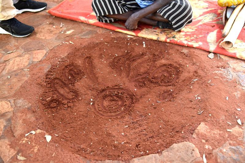 赤土で作られた伝統的なボードに指でモチーフを描きながら講習を行なう