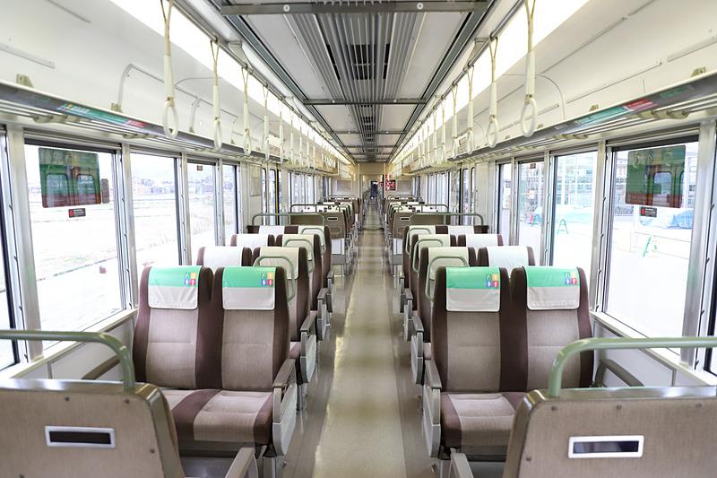写真左はAシート、写真右は新快速通常車両。壁や床、照明の色を変えたほか、つり革の撤去、シートの変更により特急列車並みの上質な空間を演出した