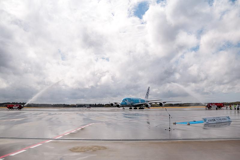 成田空港はウォーターキャノンで同機の到着を歓迎。直前まで降っていた雨は上がっていたが、注意報が出るほどの強風が吹いていたので、放水車からの水はミストシャワーのカーテンのよう