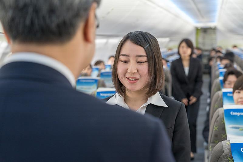 「入社おめでとうございます」と一人一人の顔を見て辞令交付する髙橋社長