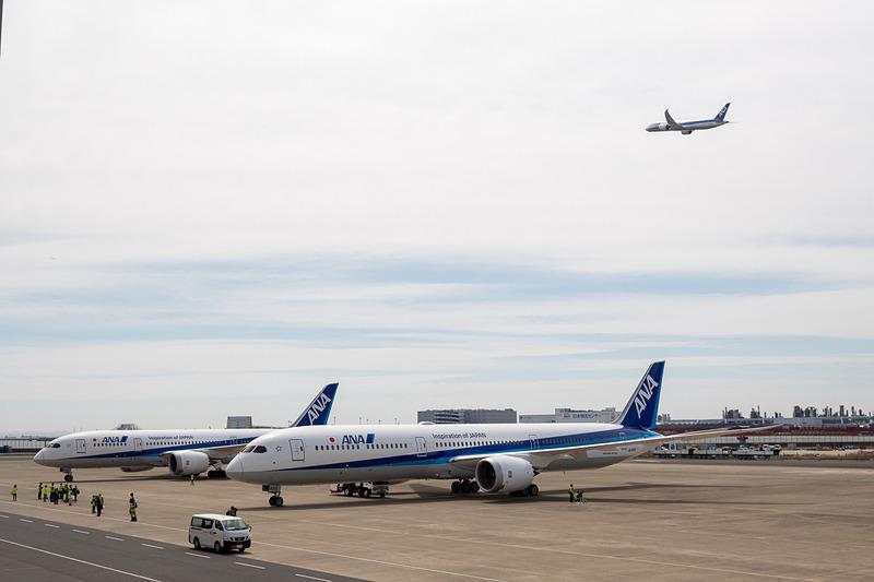 ボーイング 787-10型機(手前)、ボーイング 787-8型機(奥)が駐機する後方で離陸するボーイング 787-9型機