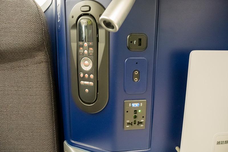 サイドテーブルに機内エンタテイメント用コントローラ、ノイズキャンセリングヘッドフォン端子、電源類。USB電源を2つ備えるのも特徴の一つ