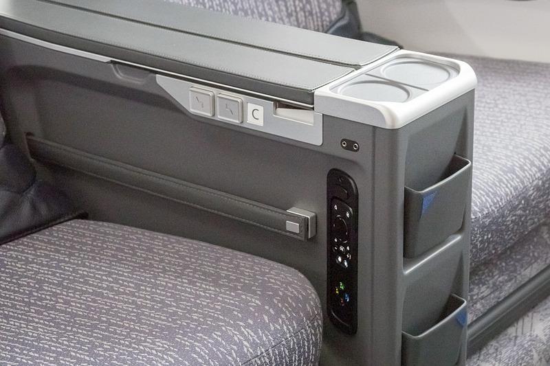 アームレストの下に収納ポケット。側面に機内エンタメのコントローラや、背もたれ&レッグレストのロックを解除するためのボタンを備える