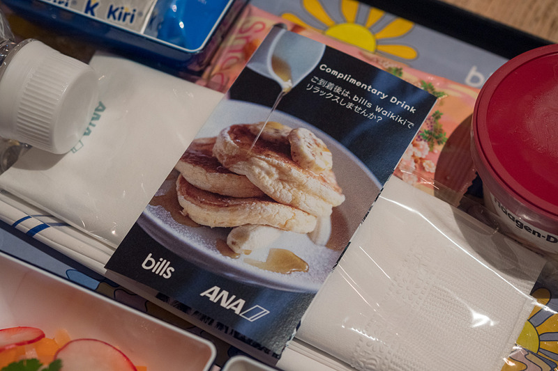コラボレーション機内食のトレイに乗るカード。bills Waikikiに持参して料理を楽しむ際に、ウェルカムドリンクをサービスしてもらえる