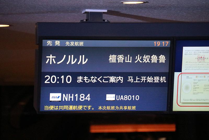 搭乗者をゲートで迎え一礼する平子社長と石田成田空港支店長。ディスプレイにはラニの画像も表示。フライト時間は7時間20分、現地は曇り、気温は23℃(摂氏)と表示されていた