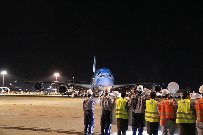 ラニのエンジンの向こうに見えるのは、FLYING HONU 2号機のカイ。機長が地上の見送りに向かい手を振ってプッシュバック。トーイングカーにもメッセージが貼られていた