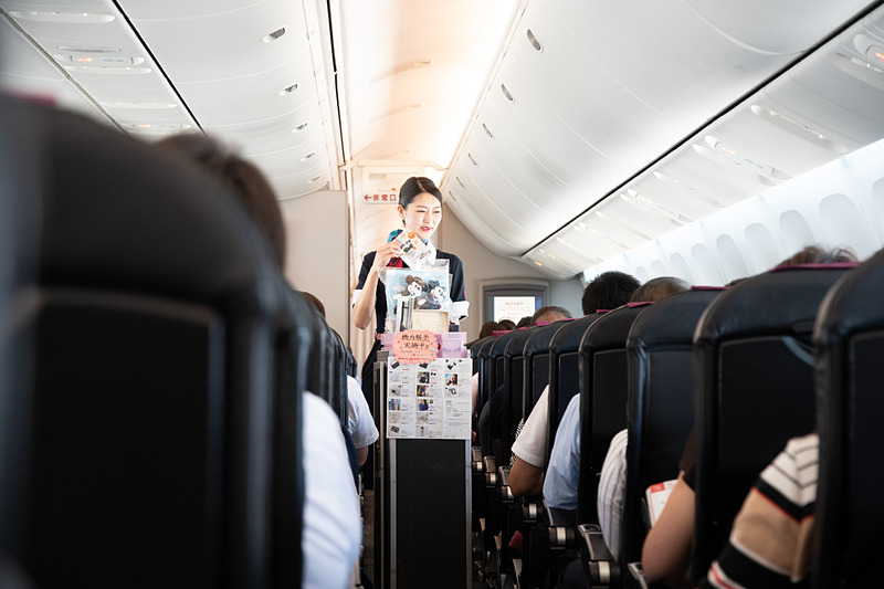 機内販売の様子。天候がよく1時間半以上飛ぶ路線であれば、機内のドリンクサービスや機内販売がゆっくり楽しめる。JALカード利用で10%引き