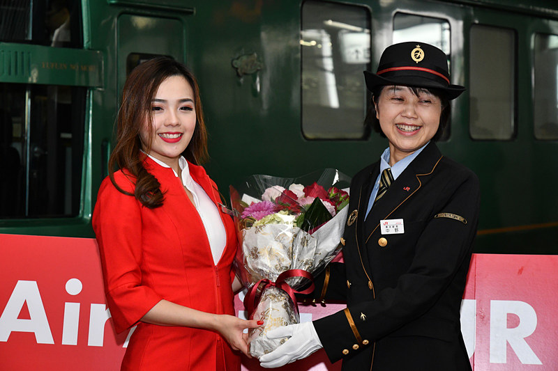 中野幹子駅長からエアアジアのCAに花束贈呈