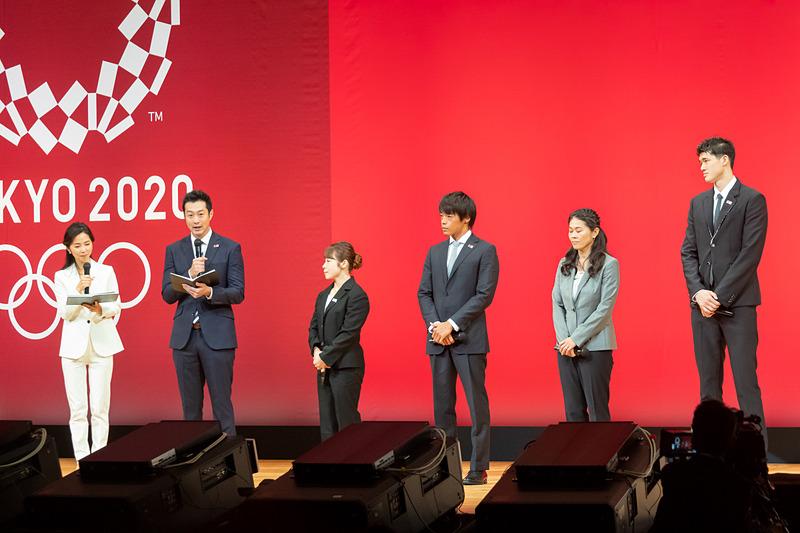 メダルデザインの発表に立ち会う三宅宏実さん、羽根田卓也さん、澤穂希さん、渡邊雄太さん。司会進行を務めるのは元NHKアナウンサーの久保純子さんと元競泳選手で北京2008大会 銅メダリストの宮下純一さん