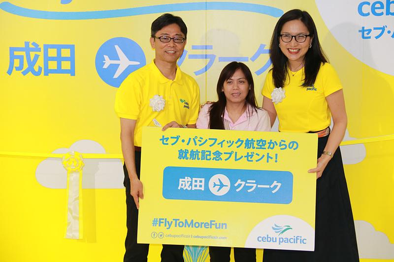 5J5069便の搭乗手続き1番の搭乗者を表彰して、セブ・パシフィック航空のイヨグ氏と松本氏から「またセブ・パシフィック航空に乗ってクラークに行ってほしいから」と航空券をプレゼント