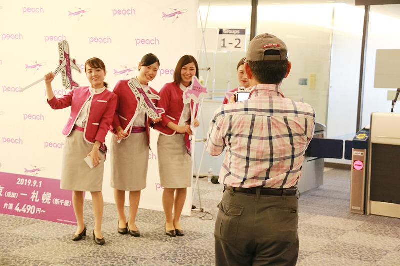 初便搭乗客に記念ステッカーをプレゼントしたり、一緒に記念撮影をするCAたち