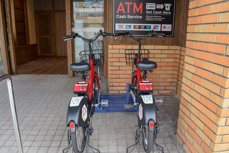 「琉球銀行イチバンジャー出張所」サイクルポートに配置されたちゅらチャリ。サドルの後ろに操作パネルがあり、ナンバーキーやICカードリーダーが配されている