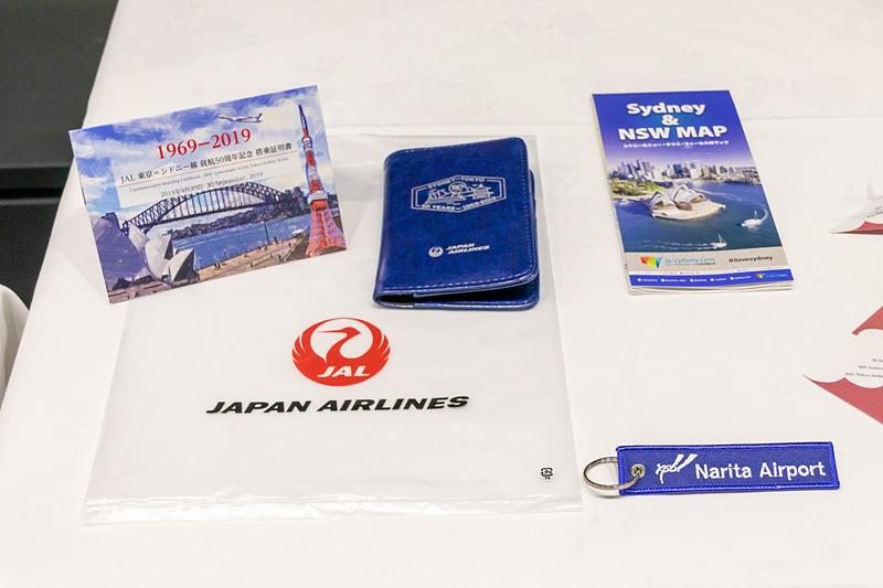 搭乗者には記念品として、搭乗記念証やパスポートケース(JAL提供)、フライトタグ(NAA提供)、シドニー ニューサウスウェールズ州マップ(ニューサウスウェールズ州政府観光局提供)が手渡された