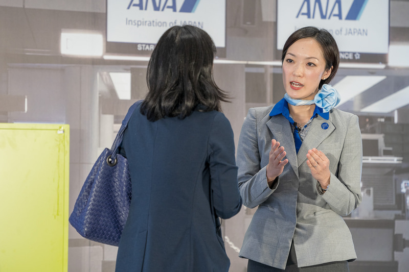 「フライトまで時間があるんだけどオススメのところは?」の質問に小松空港到着ロビーにある恐竜ロボットを紹介した小松空港の藤谷綾子さん