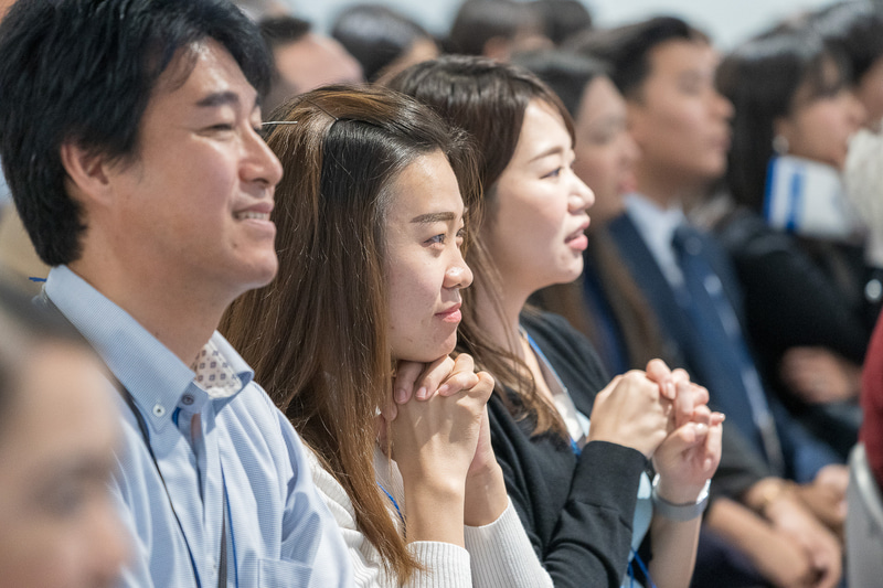 同僚のパフォーマンスを祈るような表情で応援する姿も