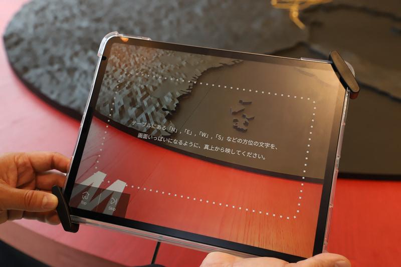 モノトーンのジオラマを撮影しているが、画面上にはカラーCGが表示される