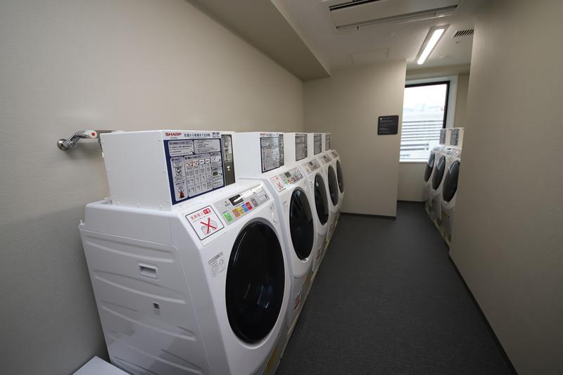 7台あるランドリーマシンは100円硬貨専用で、説明には外国語も記載。マシンの稼働状況は部屋のテレビでリアルタイムで把握できる