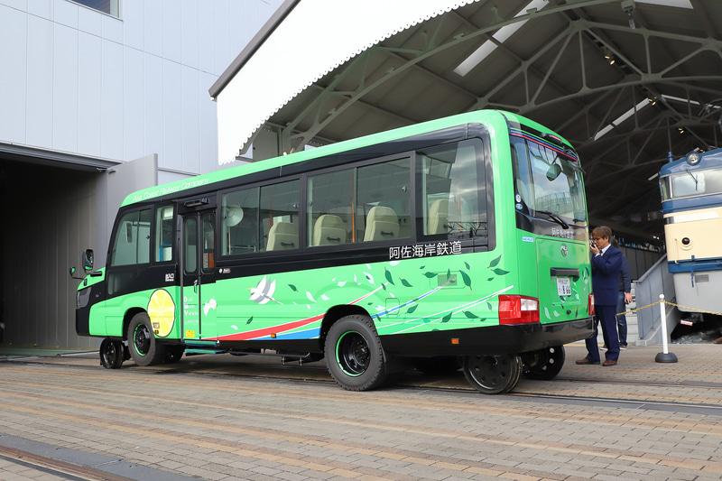 車両工場からバックで出庫する姿はマイクロバスそのもの。後輪は、線路から外れないようにするためのガイド輪で、駆動はタイヤで行なう。バスモードと鉄道モードで動力が共通なため、仕組みもシンプルになる