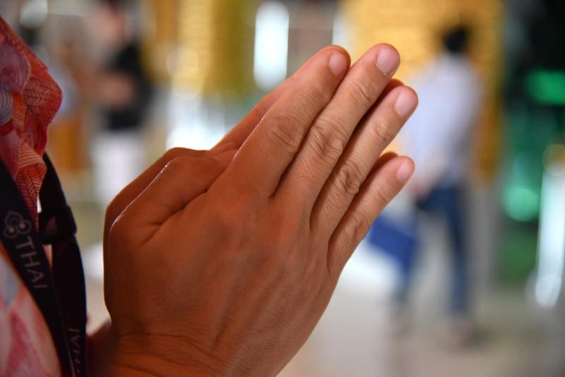 蓮のつぼみのような形に手を合わせて祈る