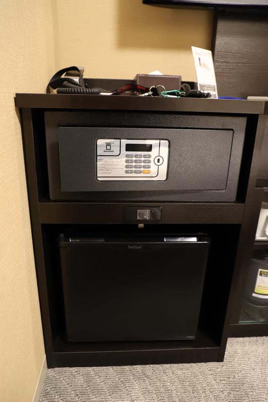 デスクサイドには金庫と冷蔵庫、湯沸かしポットとコップ、ティーバッグ