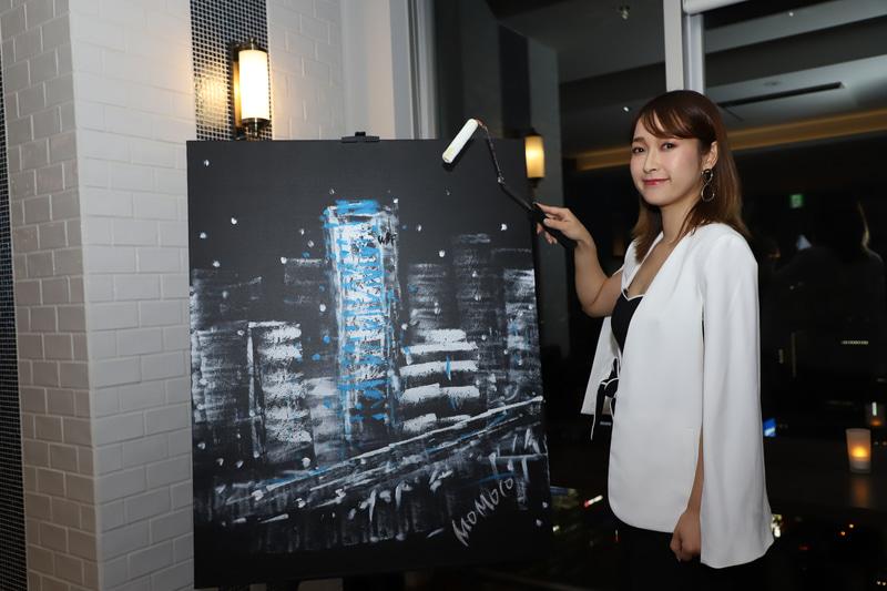 ファンションデザイナーを経て、2017年より画家としての活動を行っているMOMOCO氏。新御堂筋沿いに建ち、青のLEDで夜空に浮かぶ姿を描いた。使用する色は白と青のみ。ローラーだけで一気に描き上げていく