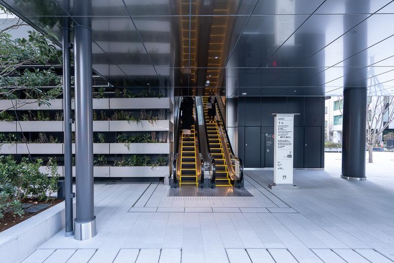 公園横に2階のデッキへのエスカレーターがある