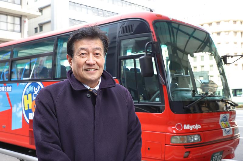 スカイホップバスマーケティングジャパン株式会社 専務取締役 中島節郎氏。背後のバスはガラスルーフタイプの従来型車両