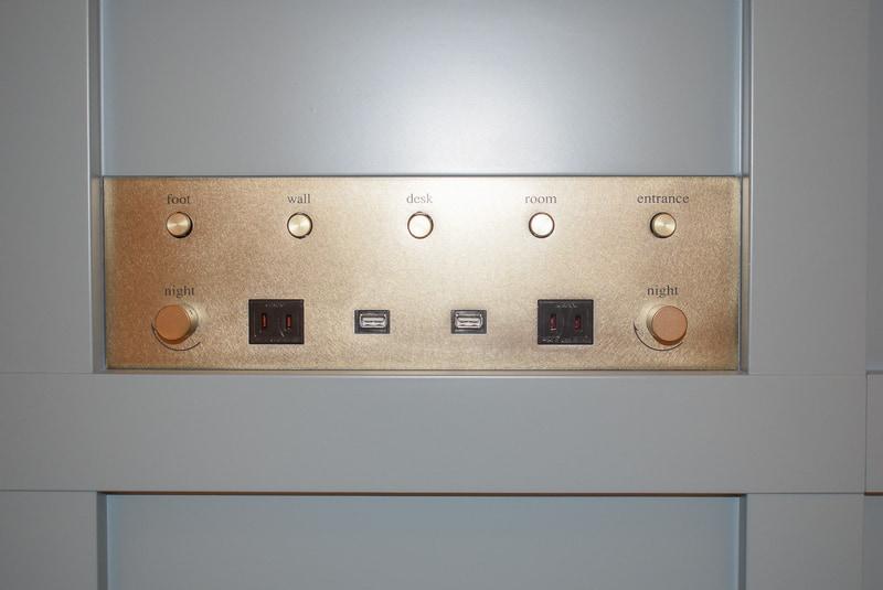 枕元に電源コンセントとUSB充電ポートを設置。写真の電源パネルの2口のほかに増設ベッド用に2口備えており、4人で泊まっても1人1口使える
