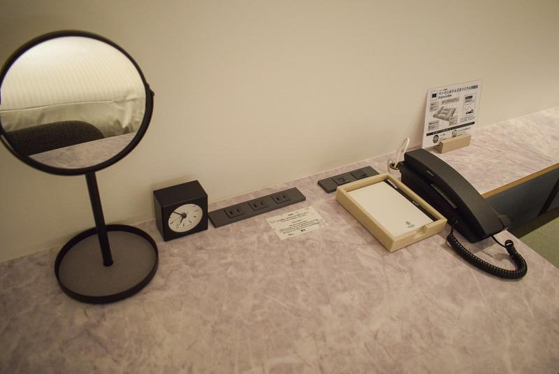 デスク回り。電話は内線のみ。メモ用紙&ボールペン、アラーム付き時計、鏡とシンプル。鏡の土台はトレー状になっているので、アクセサリー類を置くのに便利。コンセントは3口、LANのコネクタもここにある