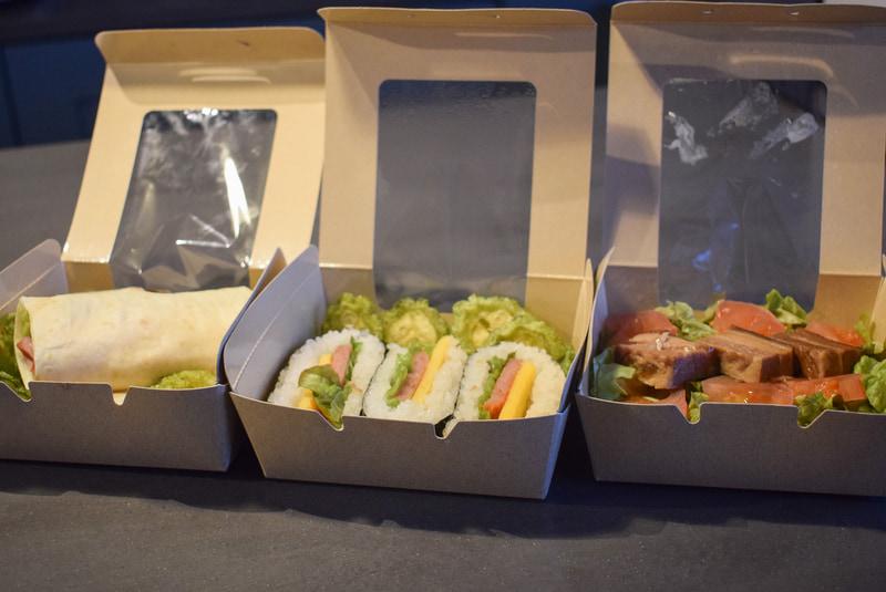 ラップサンド、スパムおにぎり、タコライスなどの軽食も用意。持ち運びしやすいようにボックスに入っている
