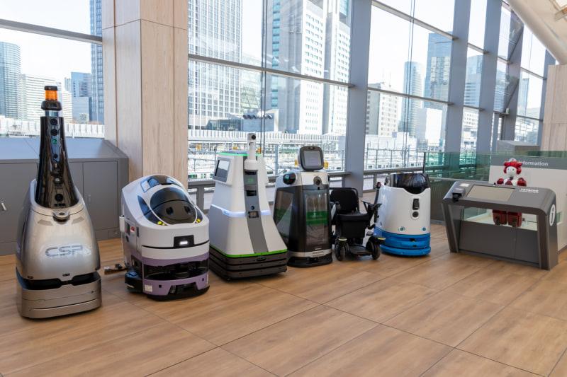 高輪ゲートウェイ駅で稼働予定の自立移動型ロボット(右端の赤いロボットは据え置き型の案内ロボット)。稼働しない日や時間帯、夜間だけのタイプもあるので、タイミングによっては見られない可能性もある