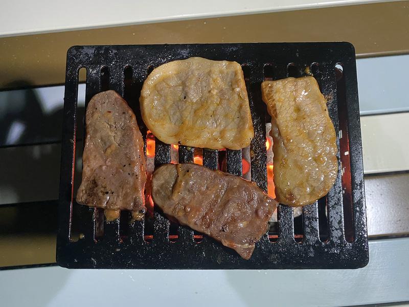 こちらはコンパクトたき火グリルである「笑's コンパクト焚き火グリル『B-6君』」で肉を焼いているところ。屋外で食べる肉はやはり別格