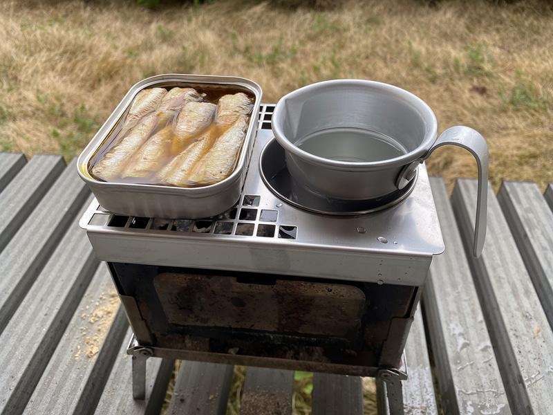 ステンレスカップを使ってお酒を湯せんで温めつつ、左側の空いたスペースでつまみを焼いたり温めたりすることができる「B-6君専用 ステンレスメッシュ カン(燗)グリル」