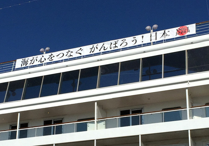 改装を終えて「飛鳥II」が「海が心をつなぐ がんばろう!日本」の横断幕を掲げて母港の横浜に停泊している