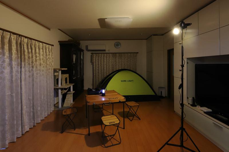 部屋の灯りを消し、仕事用のストロボスタンド+電球色蛍光灯でライトアップ。ランタンに照らされる夜のテントサイトの雰囲気をつくった