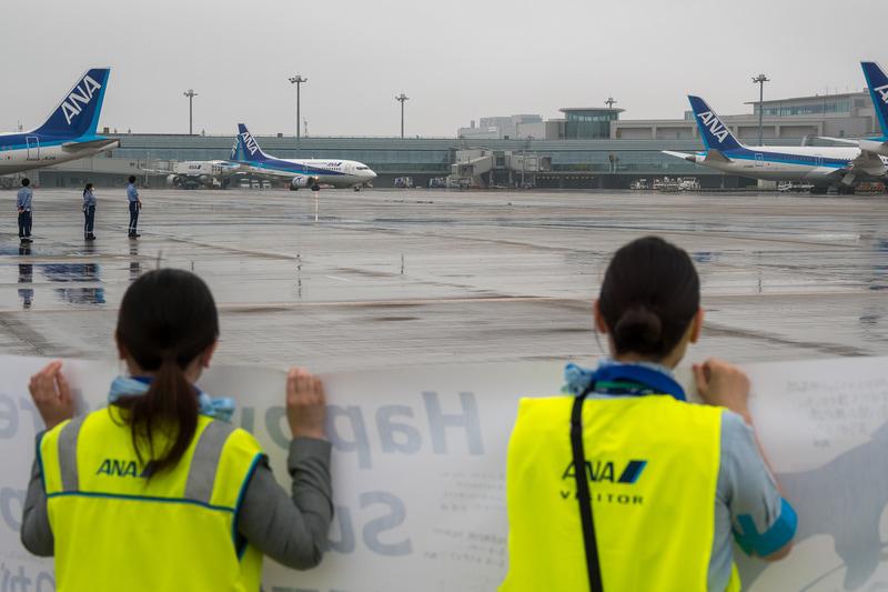 駐機場に向かうスーパードルフィンを出迎えるために横断幕を持ってスタッフが待機