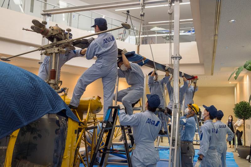 メインローターブレードの取り外し作業。ボルトを外しているのは2名だが、ほかのスタッフがブレードを支え、ネジが噛んでいる部分を緩めるためにタイミングを合わせてブレードを揺らすなどのチームワーク作業となった