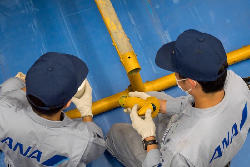 スキッドは門型リフトで機体を浮かせたうえで作業。機体左右で別の部分を取り外し、機体下部のケーブルなどをそのままに、抜き取るように取り外すことで作業の手間を抑えた