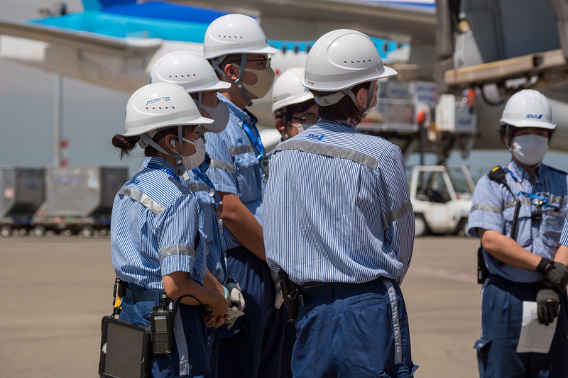 到着前にチームで集まってミーティング。日焼け防止のために長袖制服を着用するスタッフも多い