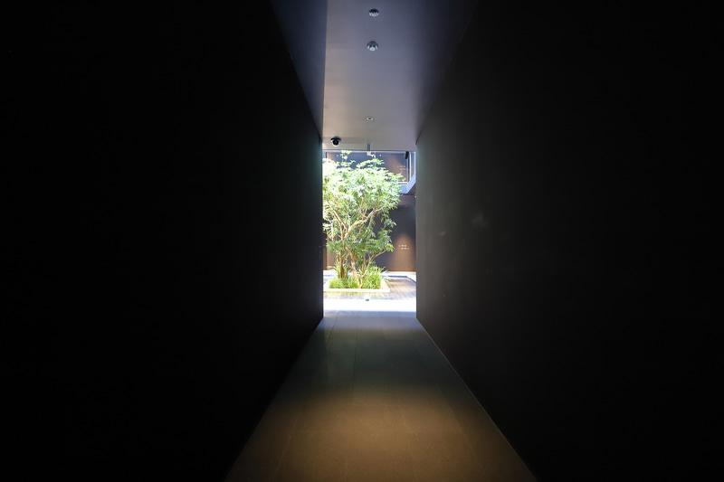 ロビー・ラウンジから客室へ向かう通路は京町家の通り庭の雰囲気。坪庭(写真奥)の水盤に反射する陽光が天井に光の紋様を描く