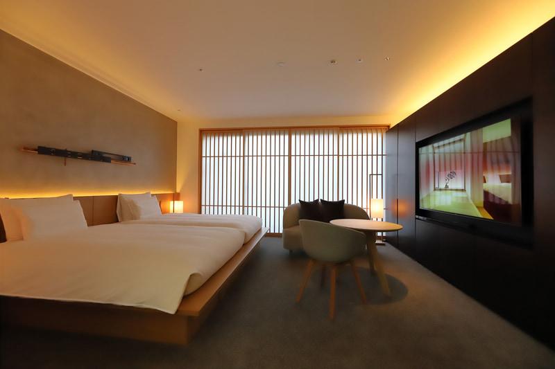「Tsuboniwa Suite」の寝室。壁や格子の窓、暗めで落ち着いたライティングなど、京町家に住んでいるかのようなデザインだ