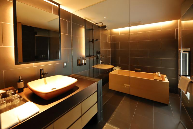黒のタイルと暖色の間接照明で洗面、バスの癒しの空間に