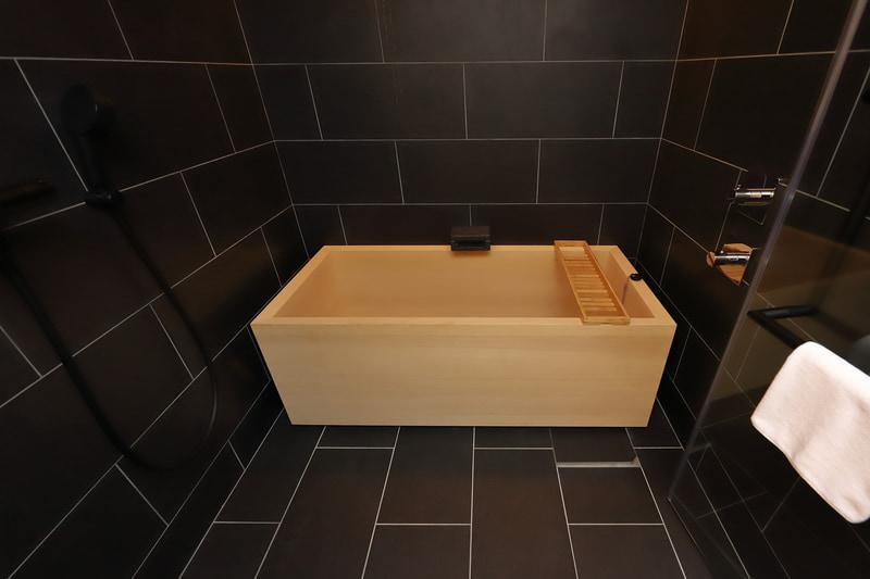 御影石づくりの漆黒の空間に真新しい檜葉の浴槽が映える。オーバーヘッドシャワーも完備