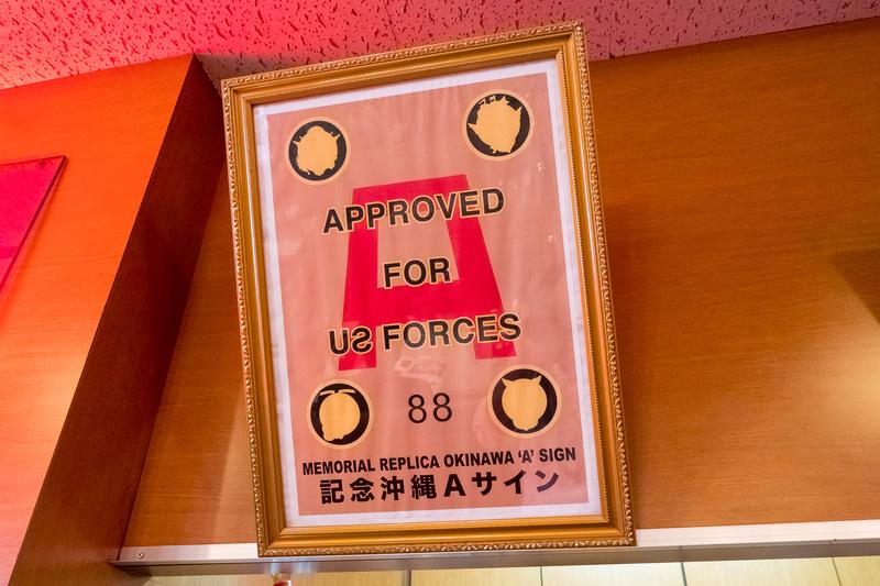 店内はアメリカンなデザイン。米統治時代の米軍による営業許可証「Aサイン」のレプリカ(写真左)も掲示されている